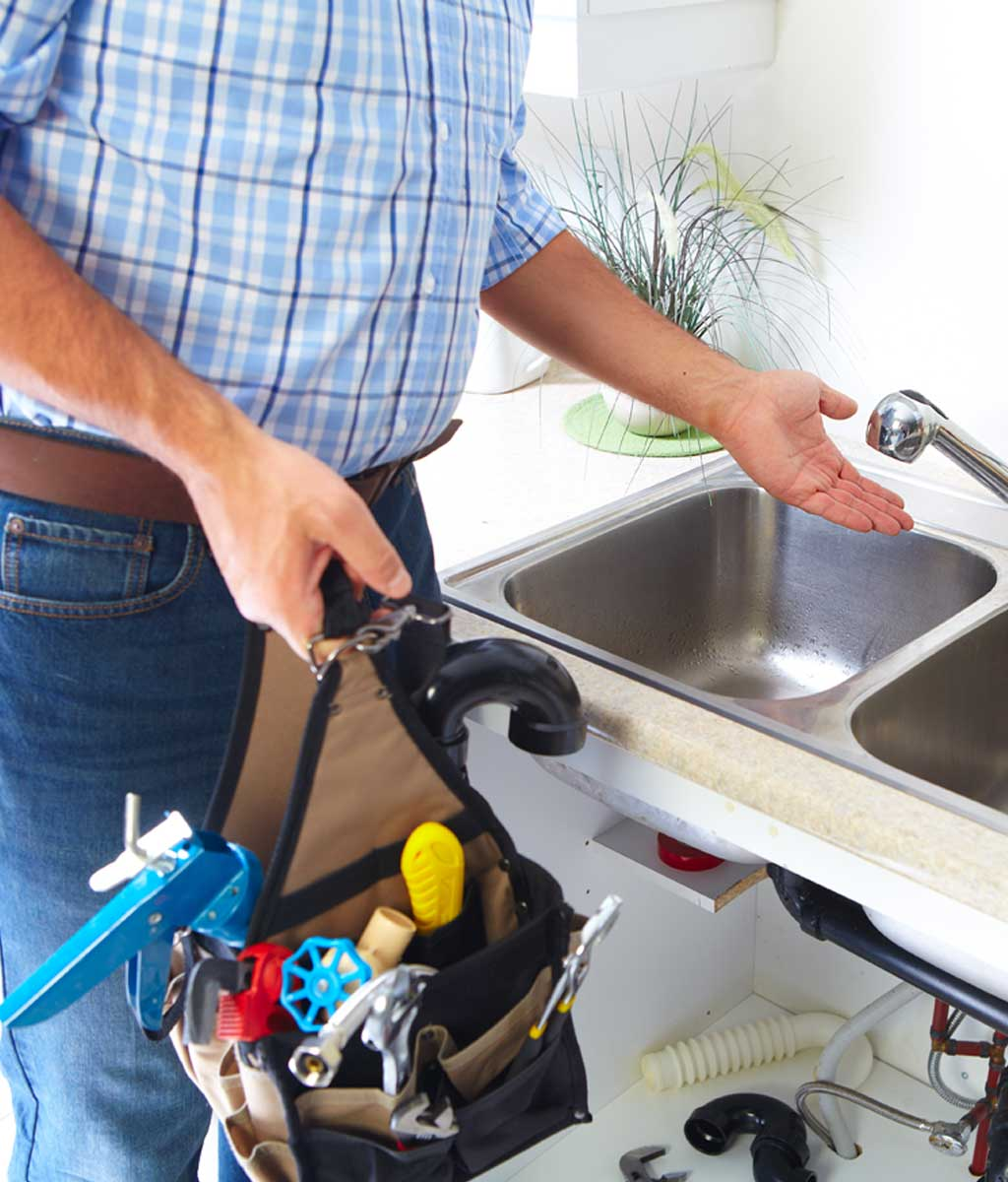 Louisville plumber working on sink with tools
